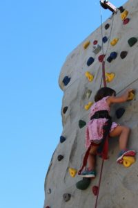 young girl on climbing wall at 2nd annual community celebration