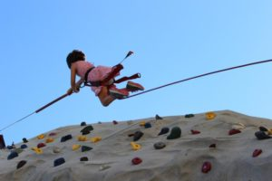 young girl repelling down climbing wall at 2nd annual community celebration