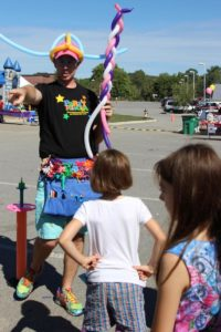 balloon man pointing at 2nd annual community celebration