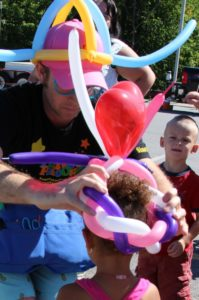 balloon man giving young girl a balloon hat at 2nd annual community celebration