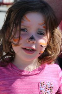 young girl with tiger face paint at 2nd annual community celebration