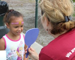 young girl admiring her face paint at 2nd annual community celebration