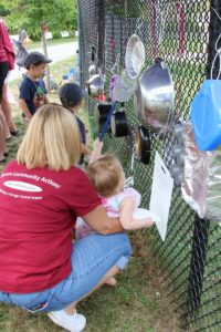 kids playing on pots and pans on a chainlink fence at 2nd annual community celebration