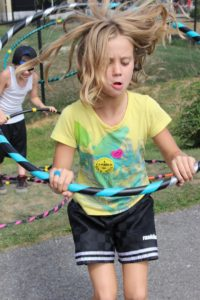 young girl playing with hula hoop at 2nd annual community celebration