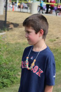 boy with cereal necklace at 2nd annual community celebration