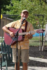 man singing with guitar at 2nd annual community celebration