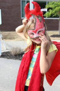 young girl in mask and devil horns at 2nd annual community celebration