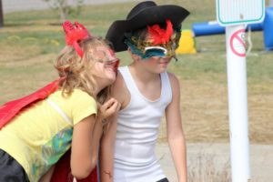 two young kids in masks at 2nd annual community celebration