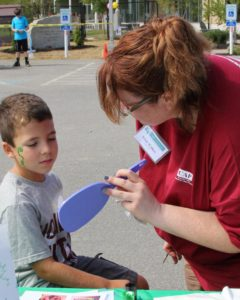 young boy viewing his face paint at 2nd annual community celebration