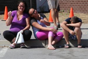three people sitting on curb at 2nd annual community celebration