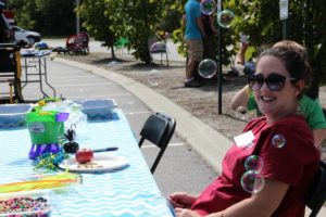 woman volunteer with bubbles at 2nd annual community celebration