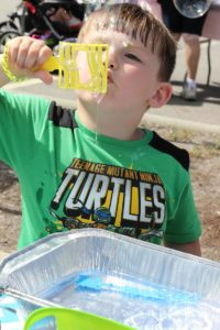 young boy blowing bubbles at 2nd annual community celebration