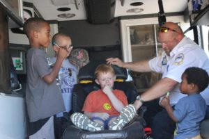 young kids hanging out in the back of an ambulance at the 2nd annual community celebration