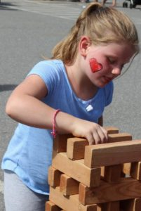 young girl playing outdoor jenga at 2nd annual community celebration