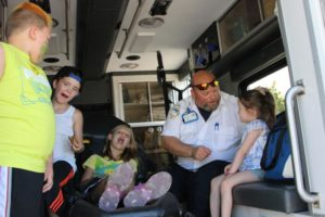kids learning about ambulances in the back of one at 2nd annual community celebration