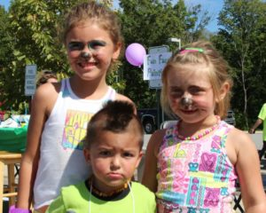 three kids with face paint at 2nd annual community celebration