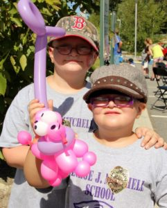 two kids with a balloon dog at 2nd annual community celebration