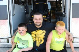 man with two boys in back of ambulance at 2nd annual community celebration