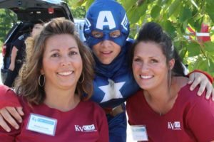 captain america with two women volunteers at 2nd annual community celebration