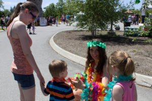 woman handing out leis to kids at 3rd annual community celebration