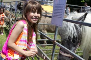 girl in front of pony at petting zoo at 3rd annual community celebration