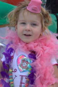 young girl in boa at 3rd annual community celebration