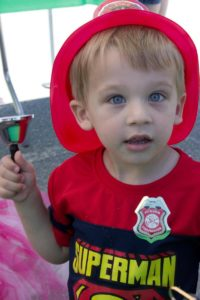 young boy in firefighter helmet at 3rd annual community celebration