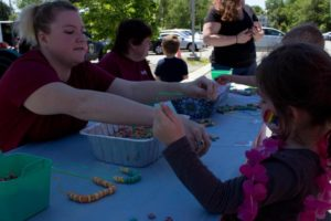 woman handing out cereal necklace to young girl at 3rd annual community celebration