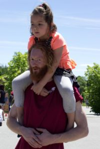 man giving piggyback ride at 3rd annual community celebration