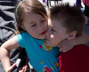 two young kids hugging at 3rd annual community celebration