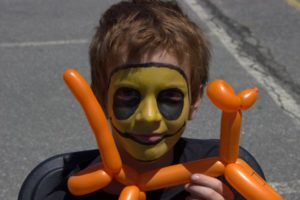 young boy in face paint with balloon animal at 3rd annual community celebration