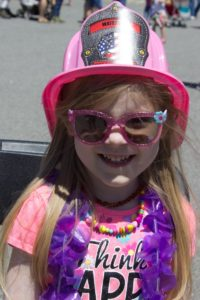 girl in pink fireman's hat at 3rd annual community celebration