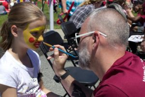 man painting young girls face at 3rd annual community celebration