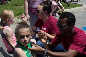 volunteers painting children's faces at 3rd annual community celebration
