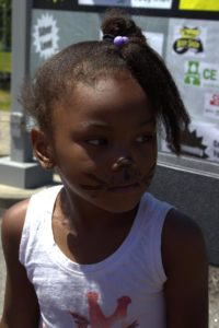 young girl in cat face paint at 3rd annual community celebration