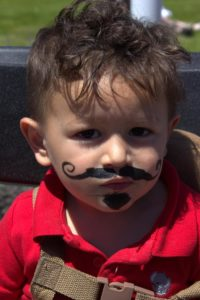 young boy with mustache at 3rd annual community celebration