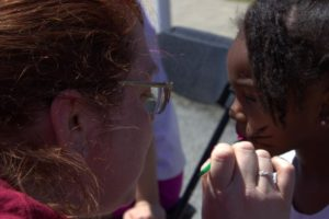 woman giving cat face paint to young girl at 3rd annual community celebration