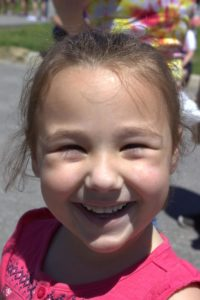 young girl smiling at 3rd annual community celebration