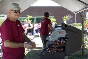 man grilling hotdogs at 3rd annual community celebration