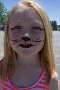 girl in cat face paint at 3rd annual community celebration