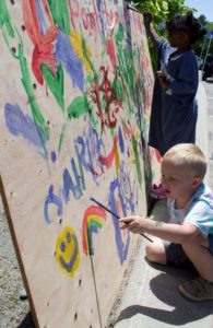 kids painting on wall at 3rd annual community celebration