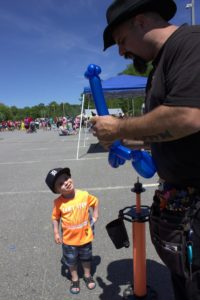 man with balloon animal and young boy at 3rd annual community celebration