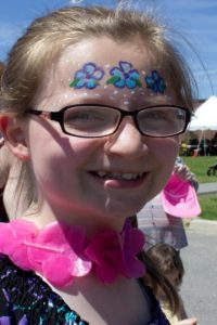 girl with flower face paint at 3rd annual community celebration