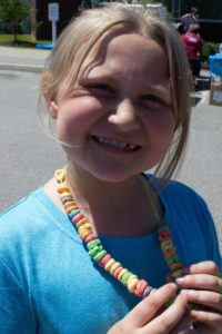 girl with cereal necklace at 3rd annual community celebration
