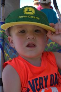 little boy in john deere hat at 3rd annual community celebration