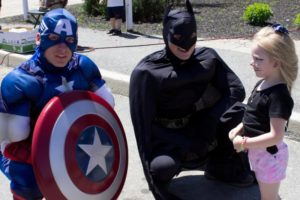 captain america, batman and young girl at 3rd annual community celebration