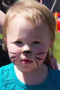 little girl with cat face paint at 3rd annual community celebration