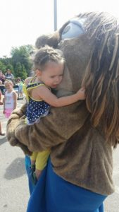 critter giving a hug to a small child at 2nd annual community celebration