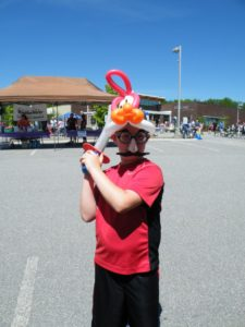 boy in balloon hat at 3rd annual community celebration