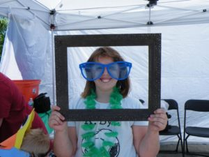girl in photo frame enjoying 3rd annual community celebration